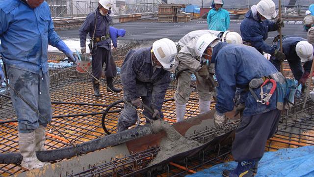 型枠にコンクリートを流し込む職人たち